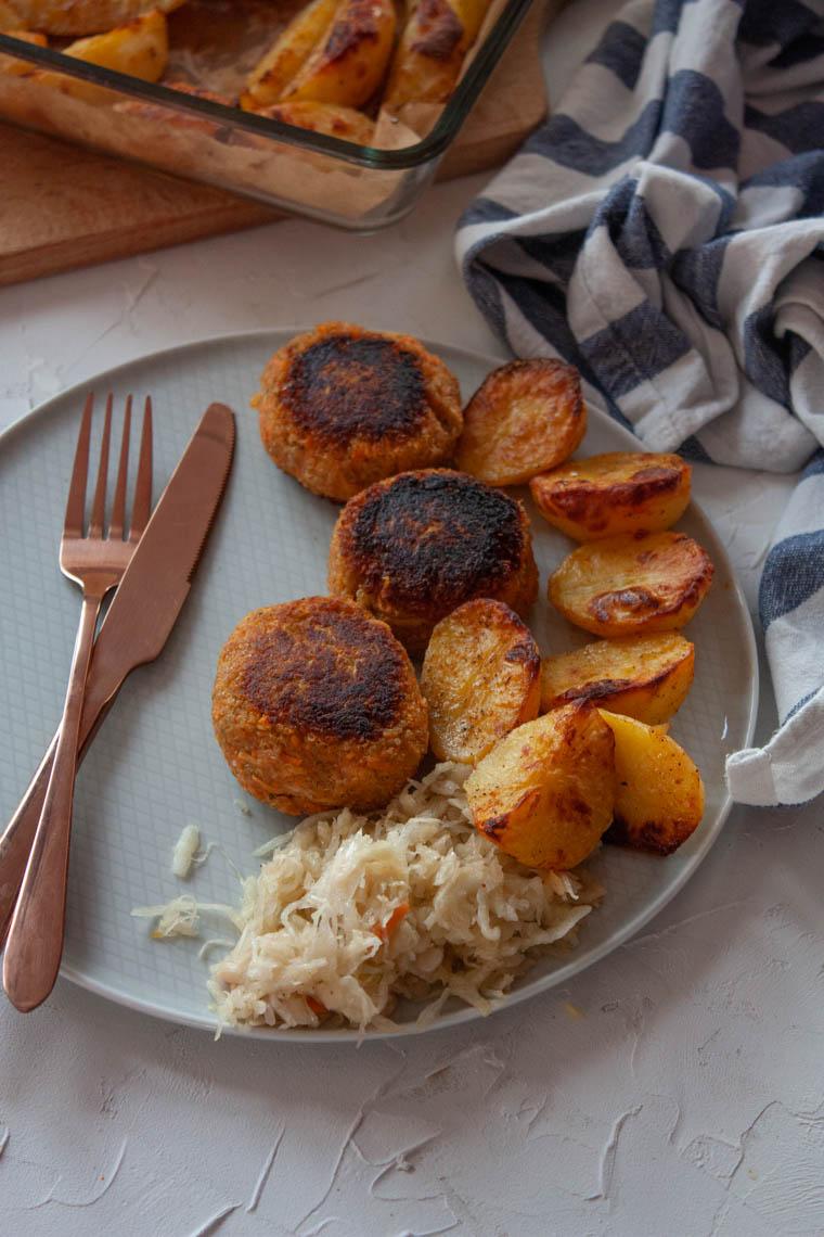 Roślinne kotlety z pieczonymi ziemniakami i surówka z kapusty kiszonej.